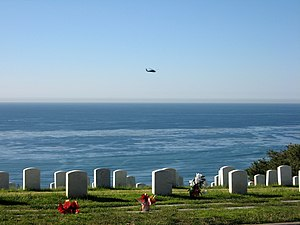 A helicopter flies past the cemetery.