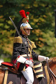 Bustul unui bărbat călare în uniformă neagră, roșie și aurie, sabie în mână și purtând o cască de aur împodobită cu un plumb roșu de pene și un cal negru lung.