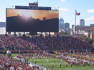 2007 Texas Longhorns football team - The Godzillatron scoreboard at Darrell K. Royal-Texas Memorial Stadium, home of the Longhorns, with the Austin skyline in the background (2006).