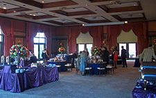 A large room with a blue carpet, windows with elaborate drawn drapes and high ceilings with recessed wood-edged panels. A few people in formal dress are either seated at round tables with large floral centerpieces, or standing around talking to each other.