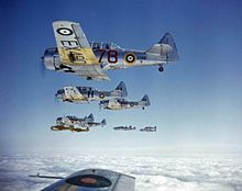 Silver fighter aircraft, marked with the British Royal Air Force's distinctive roundel, flying above the clouds in formation