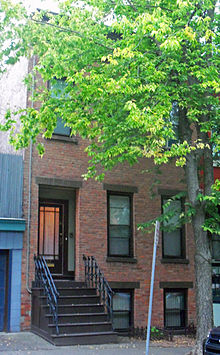 A narrow brick building with dark brown steps leading to the main entrance. Most of the upper two stories are obscured by a tree