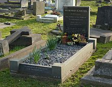 A polished, black granite headstone with freshly planted flowers, among other gravestones