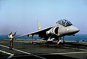Front view of two-seat grey jet fighter on aircraft carrier deck. A directive personnel is close-by.