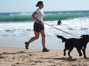 Jogging - Woman jogging with a dog on Carcavelos Beach
