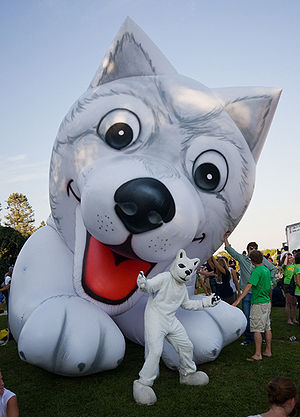 Jonathan the Husky - Jonathan (costume version) standing under a blow-up version of a husky.