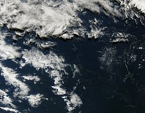 2012 Kermadec Islands eruption - Kermadec Islands pumice raft on 12 August 2012. Raft can be seen as fibrous tendrils primarily in lower right quadrant; Raoul Island can be seen as green dot near upper right.