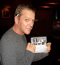 Sutherland holding a check for The 1 Second Film.