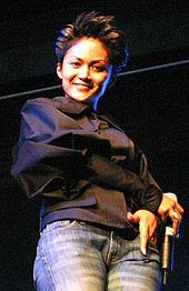An Indonesian woman, with spiked hair. She is holding a microphone and smiling