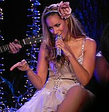 A woman is sitting whilst she sings a song. She wears a pink dress which has some fancy diamonds. She holds a microphone with her left hand, and with her right hand she points something or someone that she is looking at.
