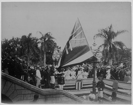 The Flag of Hawaii over `Iolani Palace is lowered following the Annexation of Hawaii by the United States (12 August 1898). Lowering the Hawaiian flag at Annexation ceremony (PPWD-8-3-006).jpg