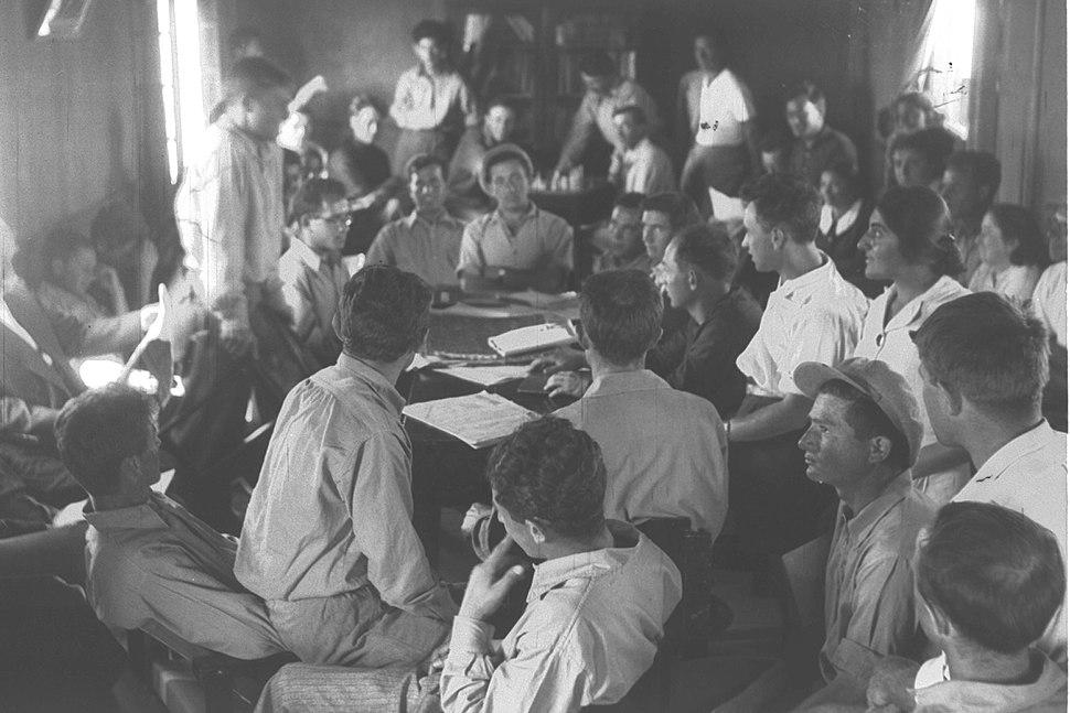 MEMBERS OF KIBBUTZ AFIKIM HOLDING THEIR GENERAL MEETING IN THE LIBRARY OF THE SETTLEMENT. אסיפה כללית של חברי קיבוף אפיקים, בספריית הקיבוץ.