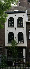 foto van Huis met smalle mergelstenen lijstgevel, voorzien van rondboogvensters boven een pui met blokwerk opzij.