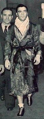 Photographie en noir et blanc d'un boxeur marchant, habillé d'un peignoir, serviette autour du cou et mains bandées.