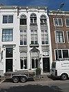 foto van Huis met geverfde gevel op natuurstenen plint aan de top afgesloten door lijst met hoekvoluten