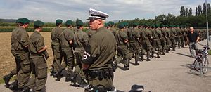 Military Police (Austria) - An Austrian MP secures and monitors marching soldiers (conscripts)