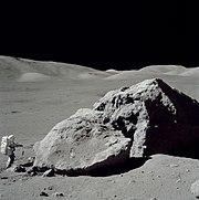 L'astronaute Harrison Schmitt se tenant debout à côté du rocher Taurus-Littrow durant la troisième sortie extra-véhiculaire de la mission Apollo 17