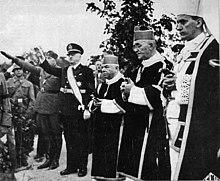 drie priesters en verscheidene saluerende mannen in militair uniform