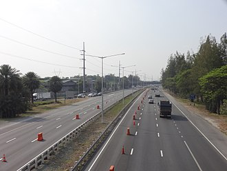 North Luzon Expressway - A typical section of NLEX near the Santa Rita interchange in Guiguinto. Streetlights can be seen on the middle of a road from where a grass median was located before the widening project in 2016. The Mexico-Balintawak transmission line of NGCP can also be seen from the highway