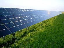 Solar panels, angled at about 30 degrees, reflect the blue sky from above a grassy field.