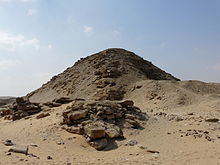A photograph of the pyramid's north and east faces. It has the appearance of a rubble mound.