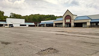 Northern Lights Shopping Center - The site of the former Hills/Ames store (left) and the former Sears store (which had been several different retailers after Sears moved out) in 2014. Note the dilapidated state at both the parking lot and the storefronts themselves. The larger structure on the right is the location of the short lived bar and nightclub Callahans's
