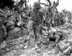 Marines pass through a destroyed small village where a Japanese soldier lies dead