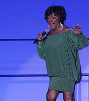 An image of an African-American woman wearing a shirt green dress whilst singing into a microphone that she is holding with her right hand. She has short black hair and is also wearing large silver earrings.