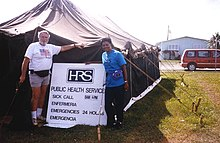 Two people standing outside a large black tent, beside a sign reading 'HRS public health services. Sick call Enfermeria 8am–6pm. Emergencies Emergencia 24 hours.'