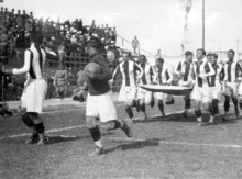 Photo of ten men, running and carrying a large flag, inside a stadium