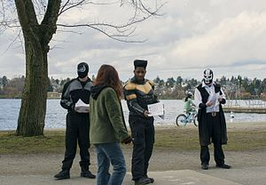 Real-life superhero - Phoenix Jones and members of the Rain City Superhero Movement pass out flyers with a description of a wanted criminal in Seattle area