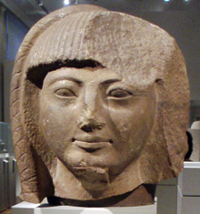 Large head of a statue in light brown stone