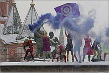 Eight women wearing colorful summer clothes and knit ski masks stand on a snowy stage. One is playing a guitar, another waves a purple flag with a combination woman symbol-raised fist, and another holds a smoke bomb emitting a purple-blue plume of smoke.