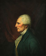 Portrait of a determined-looking man with white hair. He looks to the viewer's left with his head in profile.