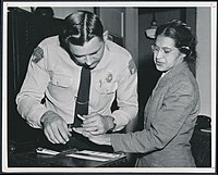 Rosa Parks being fingerprinted by Deputy Sheriff D.H. Lackey after being arrested on February 22, 1956, during the Montgomery bus boycott - Original.jpg