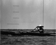 A man wearing a broad straw hat is rowing an outrigger dugout canoe has seen the periscope of the nuclear submarine USS Triton