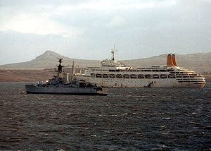 Small grey ship and larger white ship, with mountain in background