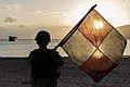 Sailor waves the Uniform flag, guiding a landing craft utility to shore. (37207237995).jpg