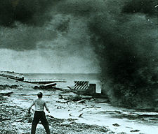 A man stands on a crumbled roadway by a body of water. The road is filled with bricks and pieces of broken concrete lying around. The man is tense, facing a large, black, smoke-like wave of water that fills the upper right-hand portion of the picture. The man looks frightened and his legs are bent, spaced apart, as if preparing to run or sprint.