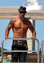 A shirtless man wearing a hat and jeans.