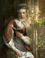 A woman in folk costume reading.