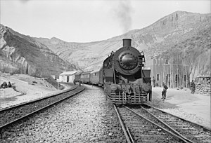 Persian Corridor - An American train transporting aid bound for the USSR stopping at a station. Supplies moved by road, rail and air through the Persian Corridor. c. 1943