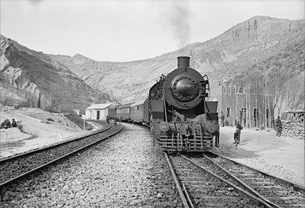 An American train transporting aid bound for the USSR stopping at a station. Supplies moved by road, rail and air through the Persian Corridor. c. 1943 Somewhere in Iran. An American engine transporting allied aid for Russia, stopping at a station rimmed by mountains.jpeg