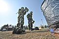 South Korean service members, clad in mission oriented protective posture suits, remove their gas mask carriers and helmets during counter chemical, biological, radiological, nuclear and explosive (CBRNE) 120229-F-RB551-072.jpg