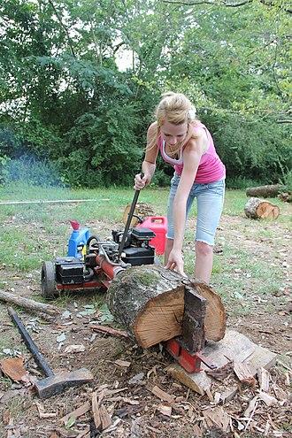 Log splitter - A woman using a gas powered log splitter to split firewood.