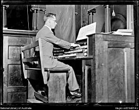 A black and white photo of a man playing the organ showing the keyboard and the pedals