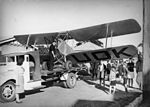 StateLibQld 2 194807 VH-UOK biplane being loaded onto a carrier's truck, 1939.jpg