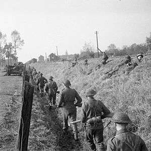 160th Infantry Brigade and Headquarters Wales - Infantrymen of the 4th Battalion, Welch Regiment advance along a railway embankment during the capture of 's-Hertogenbosch, the Netherlands, 25 October 1944.