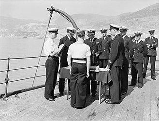 """Master-at-arms - On board HMS Rodney, the master-at-arms (left) reads out the names at the """"captain's defaulters and requestmen"""" parade (a type of court martial for minor offences), during World War II"""