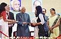The Vice President, Shri M. Hamid Ansari presenting the Vidyadhanam scholarship to a student, at the inauguration of the 4th phase of the Vidyadhanam project, at Kochi, Ernakulam, in Kerala.jpg